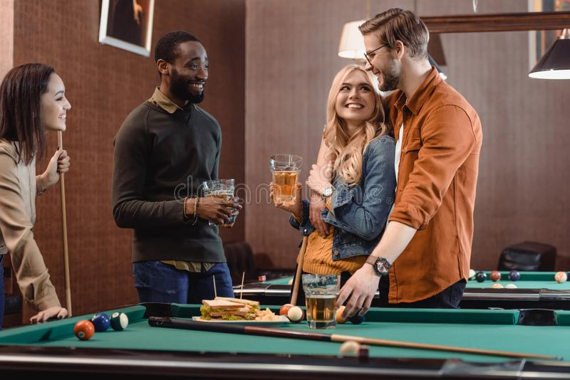 Company of multiethnic friends eating and drinking beside pool table. At bar stock images