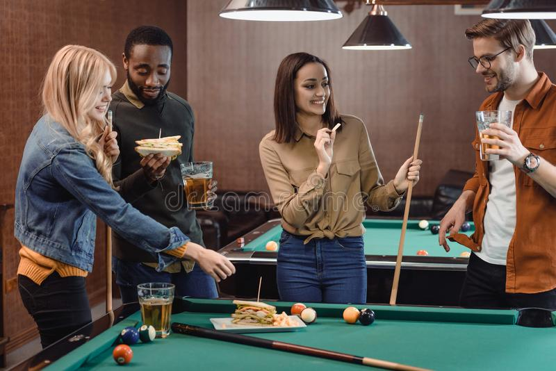 Company of multiethnic friends eating and drinking beside pool table. At bar royalty free stock photo