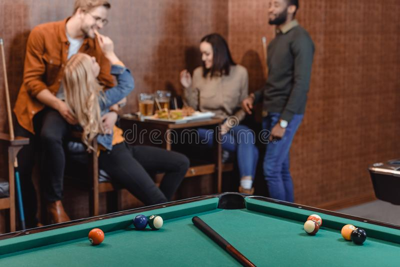 Company of multiethnic friends eating and drinking beside pool table. At bar stock photo