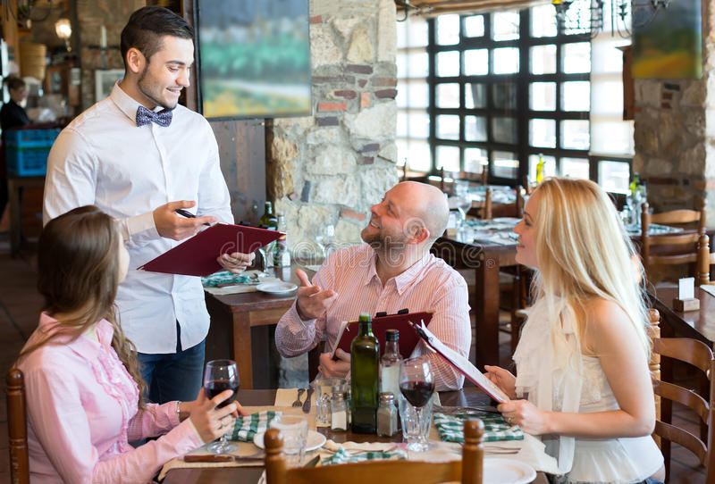 Company ordering food in restaurant. Man and two women ordering food in a restaurant. Smiling waiter is taking their order stock photography