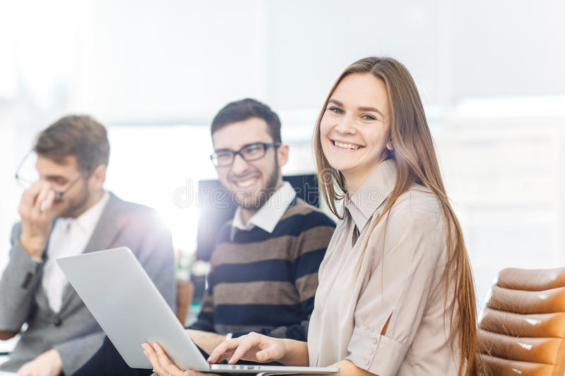 Company`s employees with a laptop sitting in the lobby of the modern office stock image