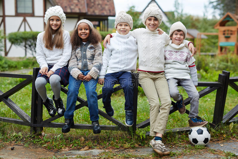 Company of schoolkids. Affectionate youngsters sitting in row outdoors royalty free stock photography