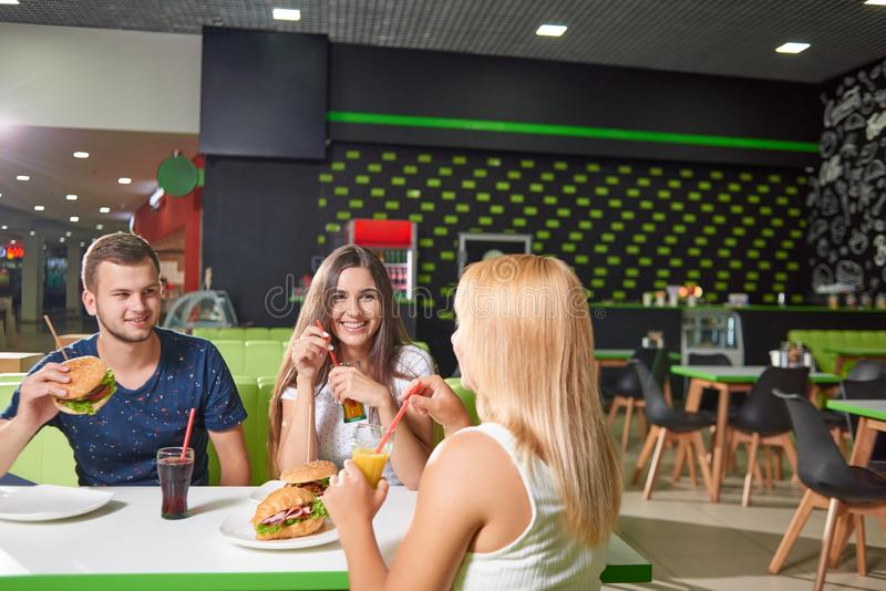 Company sitting at cafe and eating yummy fast food. And drinking juice. Happy boy and young brunette looking at blonde sitting opposite and laughing. Concept of stock photography