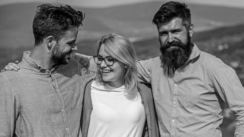 Company of three happy colleagues or partners hugs outdoor, nature background. Men with beard in formal shirts and stock photos