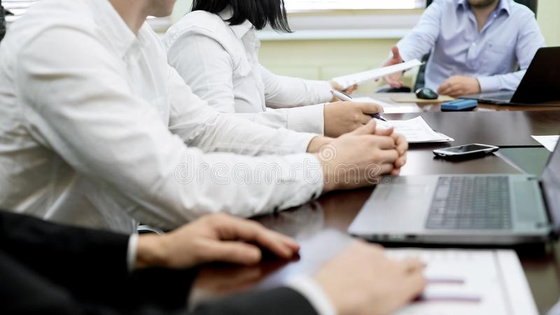 Company workers sitting at table at business meeting, listening to chief speech royalty free stock images