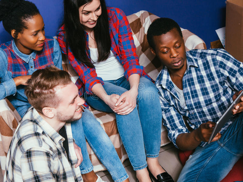 Company of young friends on couch at home, closeup stock image
