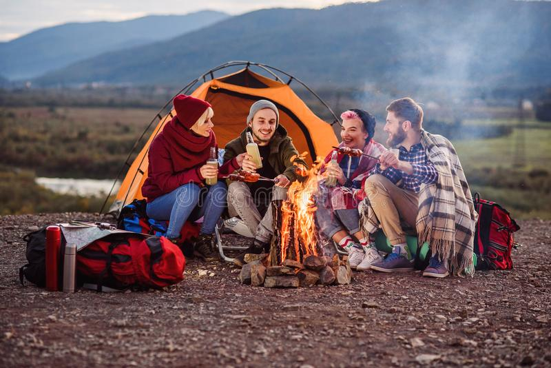 Company of young friends having a picnic by the mountains, they are chatting, laughing, drinking energy drink and bake stock photography
