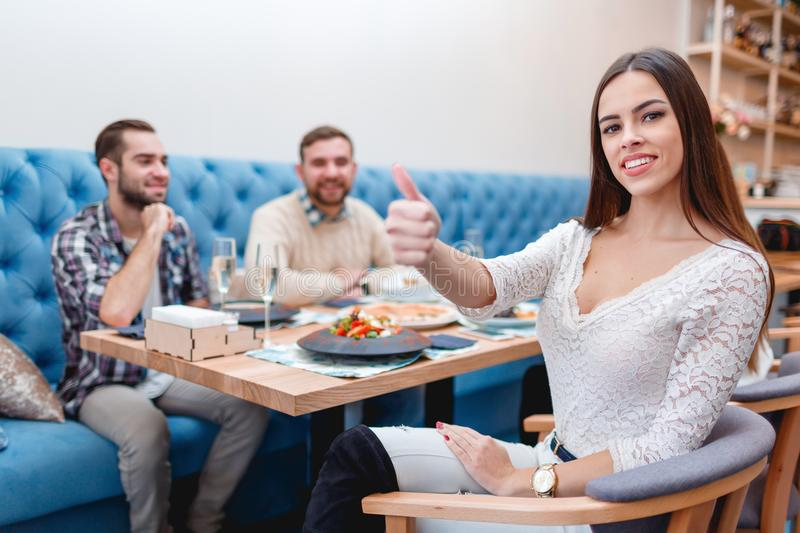 The company of young guys and girls in a cafe, the girl smiles and shows her thumb up. stock photo