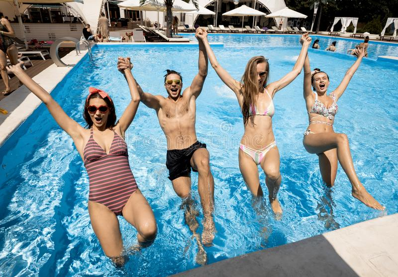 Company of young merry girls and guy jump together holding hands in the swimming pool on the open air on a sunny summer royalty free stock photo