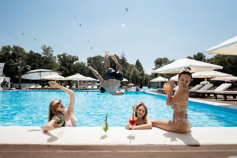Company of young merry girls and guy are relaxing in the swimming pool, drinking cocktails and jumping in the water on. The open air on a sunny summer day stock photography