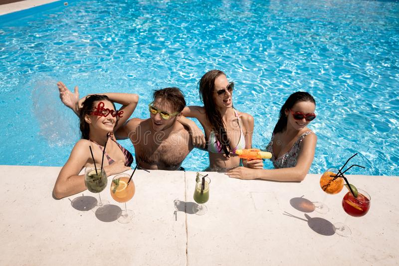 Company of young merry girls and guy relaxing in the swimming pool, drinking cocktails and playing with water guns on. The open air on a sunny summer day stock images