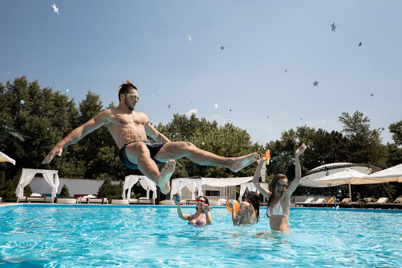 Company of young merry girls and guy relaxing in the swimming pool, jumping in the water and playing with water guns on. The open air on a sunny summer day next stock image