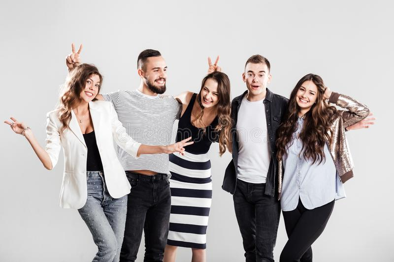 Company of young people dressed in stylish casual clothes smile and have fun together on a white background in the royalty free stock photos