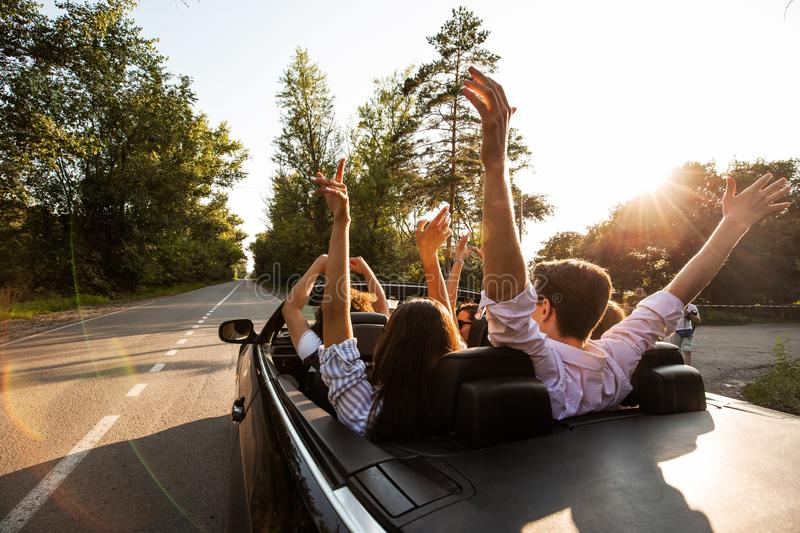 Company of young people riding in a cabriolet on the road and holding their hands up on a warm sunny day. Back view. royalty free stock images