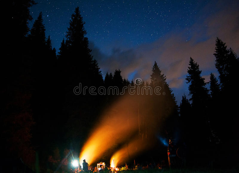 The company of young people are sitting around the bonfire and singing songs. Tourist camp under starry night sky . Travel concept stock image