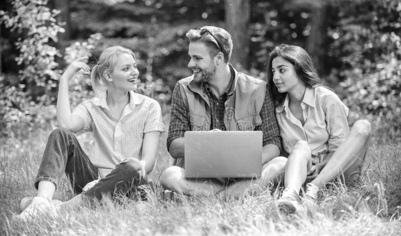 Company youth spend leisure outdoors with laptop. Friends working with laptop at green meadow. Freelance opportunity royalty free stock photos