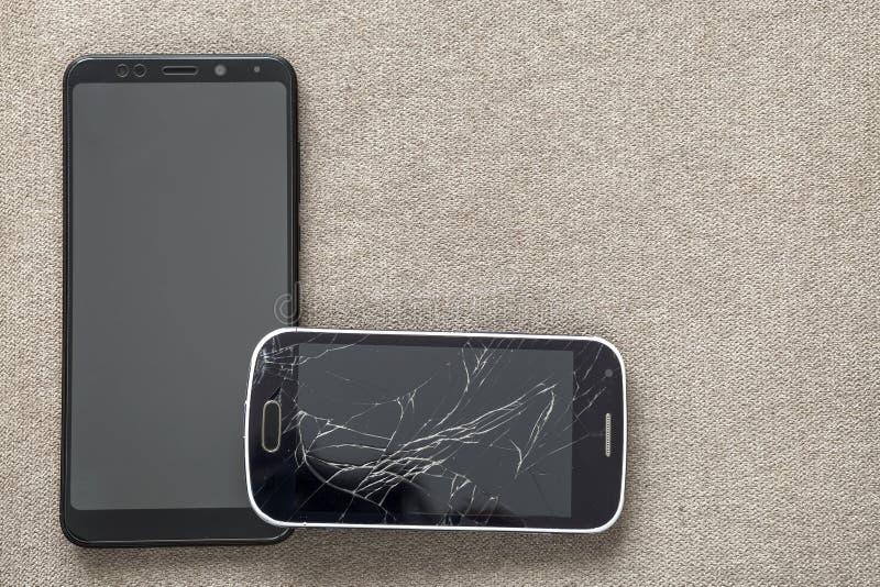 Comparación de dos teléfonos móviles negros, del teléfono móvil viejo con la pantalla agrietada y de nuevo moderno en fondo liger foto de archivo libre de regalías