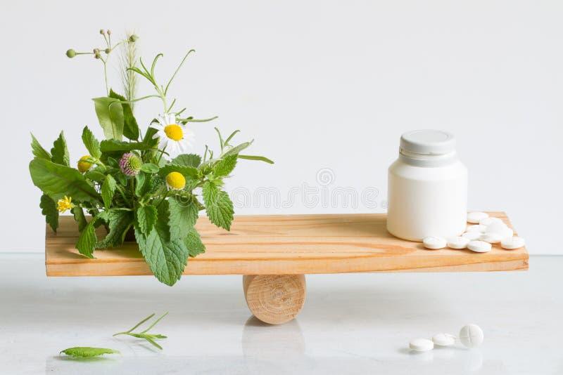 Comparación de la balanza del peso de la medicina alternativa o de las píldoras con las tabletas y las hierbas fotos de archivo libres de regalías