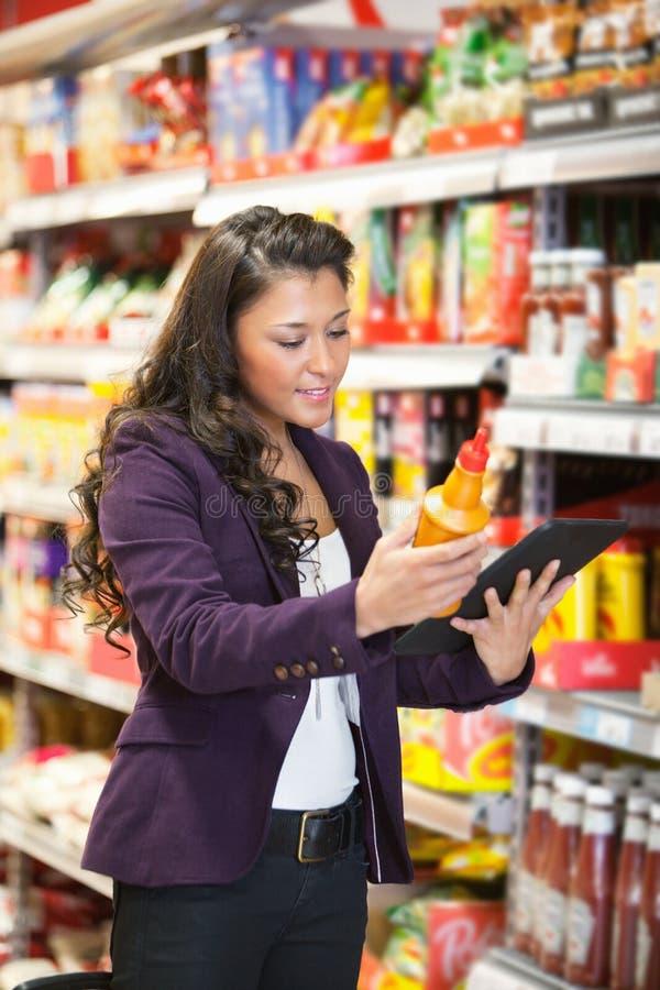Comparación en línea del producto en supermercado imagenes de archivo