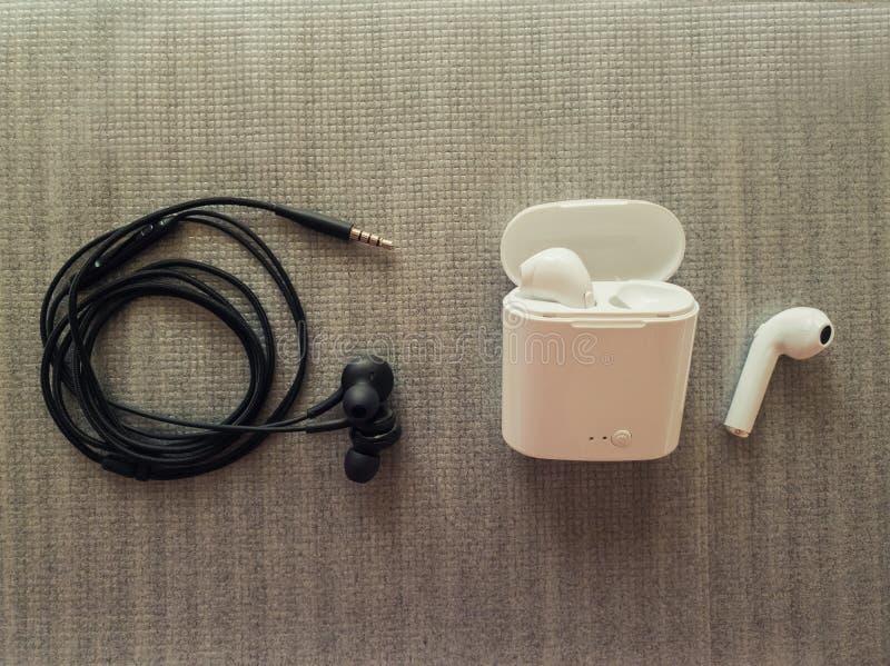 Comparación entre 3 el enchufe de 5m m ató con alambre los auriculares contra los auriculares inalámbricos para la música que esc imagen de archivo libre de regalías