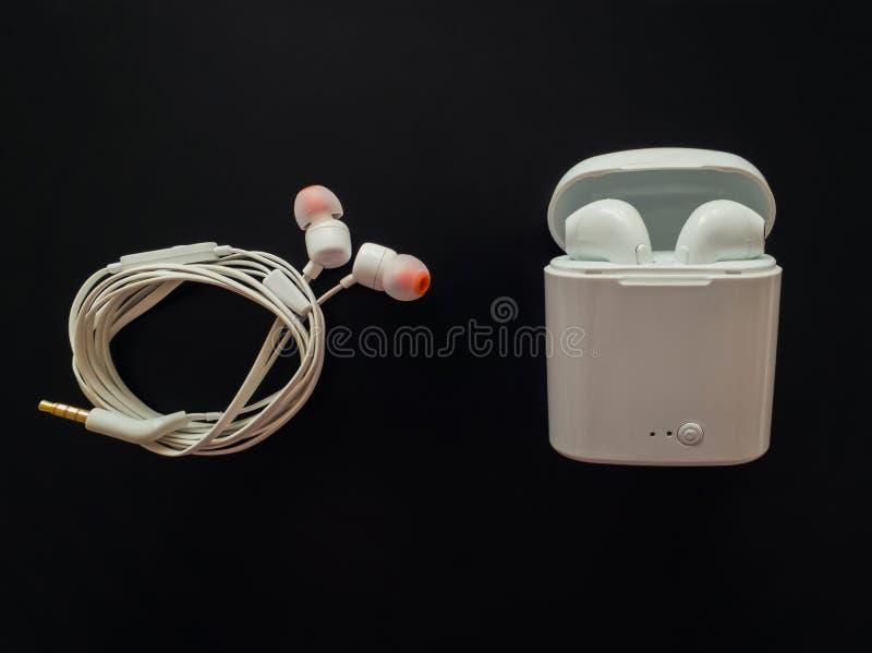 Comparación entre los auriculares atados con alambre clásicos contra los auriculares inalámbricos, vainas del aire, aisladas sobr fotografía de archivo