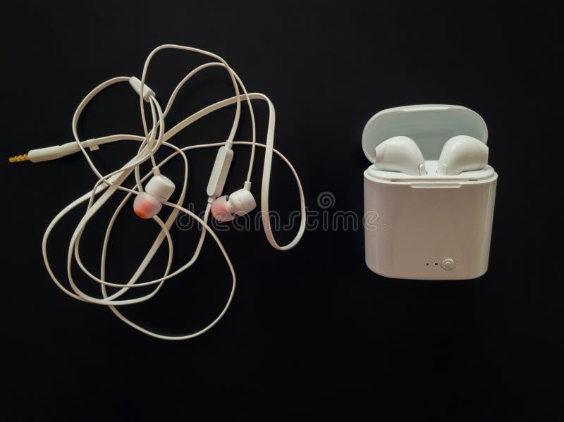 Comparación entre los auriculares atados con alambre enredados contra los auriculares inalámbricos para la música que escucha Pro foto de archivo libre de regalías