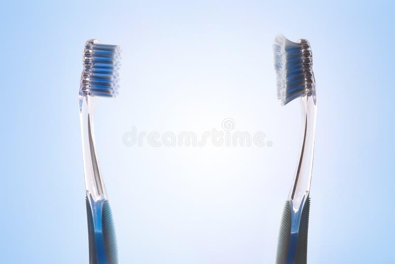 Comparación entre nuevo y usado hacer frente del cepillo de dientes imagen de archivo
