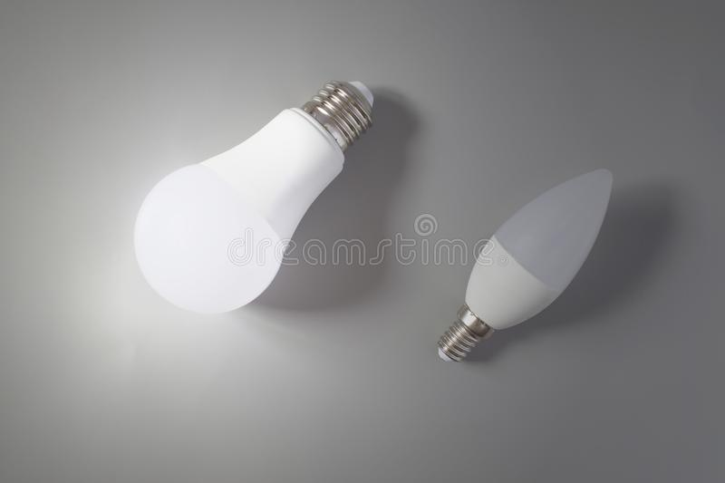 A comparative large and small light bulb, small and medium business. Lamps are on a gray background a large light is glowing stock image