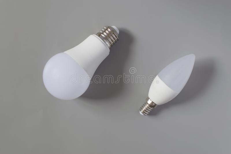 A comparative large and small light bulb, small and medium business. Lamps are on a gray background stock photo