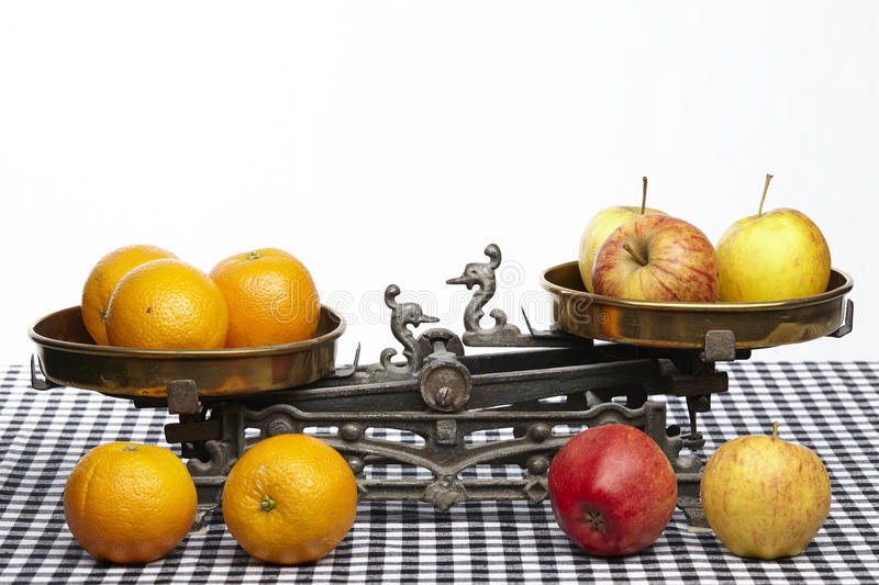 Compare apples to oranges. Apples and oranges on an old balance to visualisize the saw to compare apples to oranges royalty free stock photo