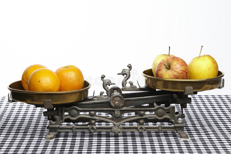 Compare apples to oranges. Apples and oranges on an old balance to visualisize the saw to compare apples to oranges stock image