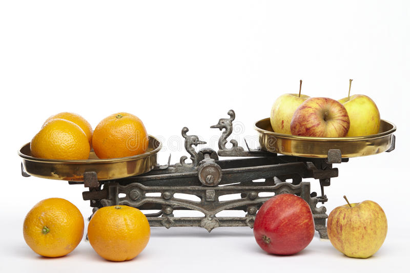 Compare apples to oranges. Apples and oranges on an old balance to visualisize the saw to compare apples to oranges royalty free stock photos