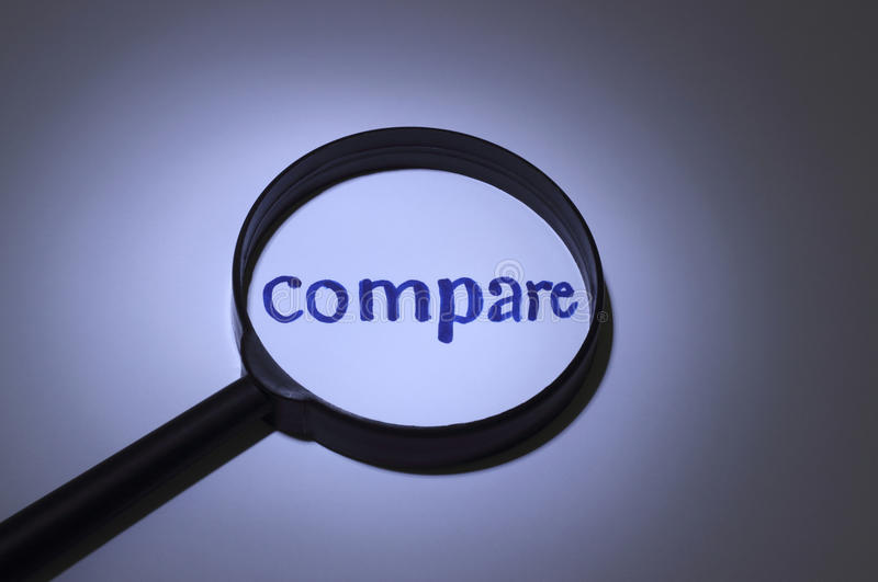 Compare. Inscription word magnified under a magnifying glass royalty free stock photo