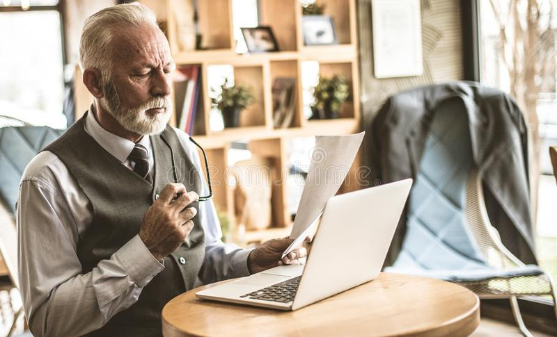 Compare plans to avoid mistakes. Senior business man working at cafe stock images