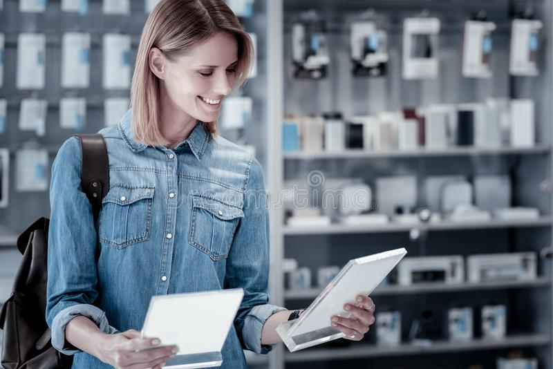 Happy young woman reading two different descriptions. Comparing descriptions. Pleasant smiling young woman looking at the descriptions of two different devices stock photos