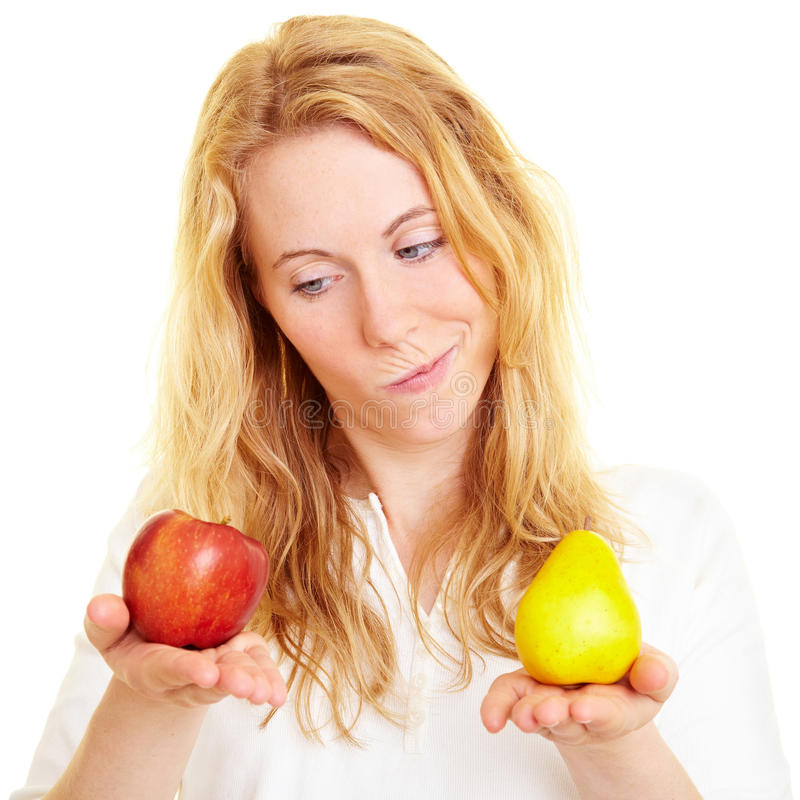 Comparing fruits. Blonde woman comparing an apple with a pear stock image