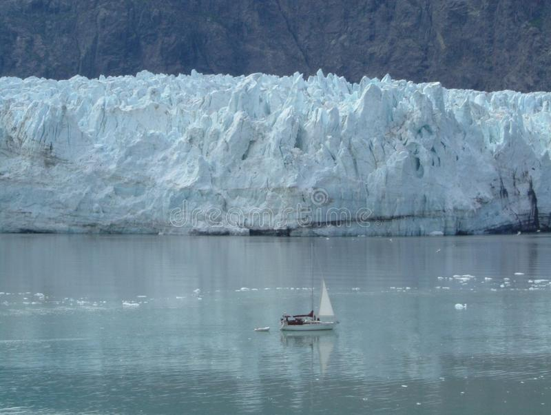 Comparison and Contrast. Sailboat up close to calving glacier stock photography