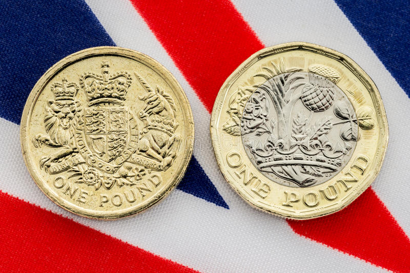 Comparison of old and new British pound coins. Tails. Comparison of old and new tails side of British pound coin on a Union Jack flag background. The new coin royalty free stock photography