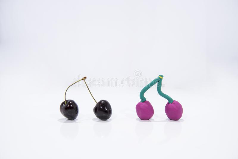 Comparison of two cherries - Real and Fake.  stock photography