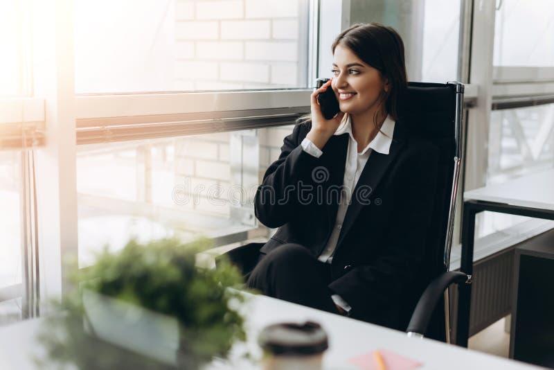 Compartilhando de boas notícias de negócios Jovem mulher atrativa que fala no telefone celular e que sorri ao sentar-se em seu lu imagens de stock royalty free