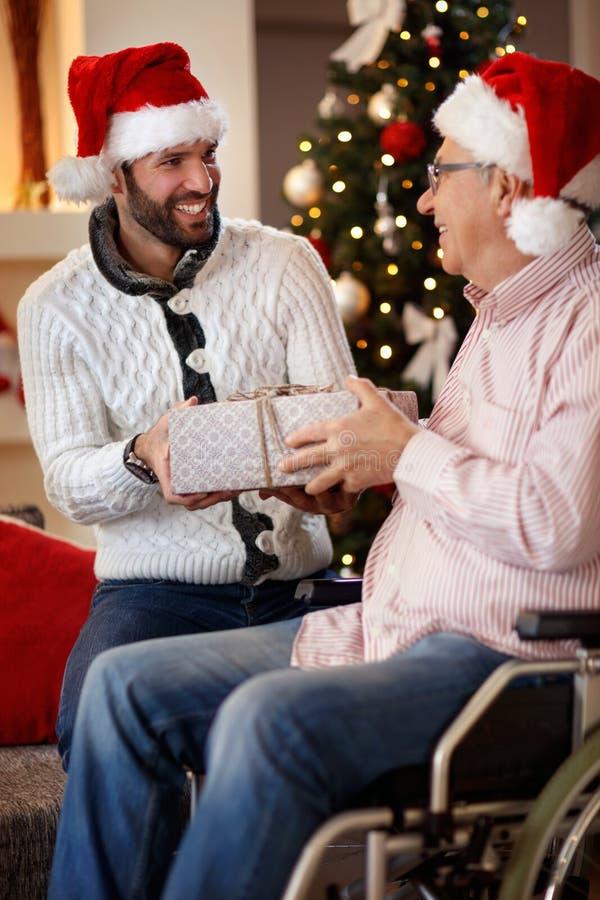 Compartilhando do presente na doação de sorriso do filho do Natal atual ao pai fotos de stock royalty free