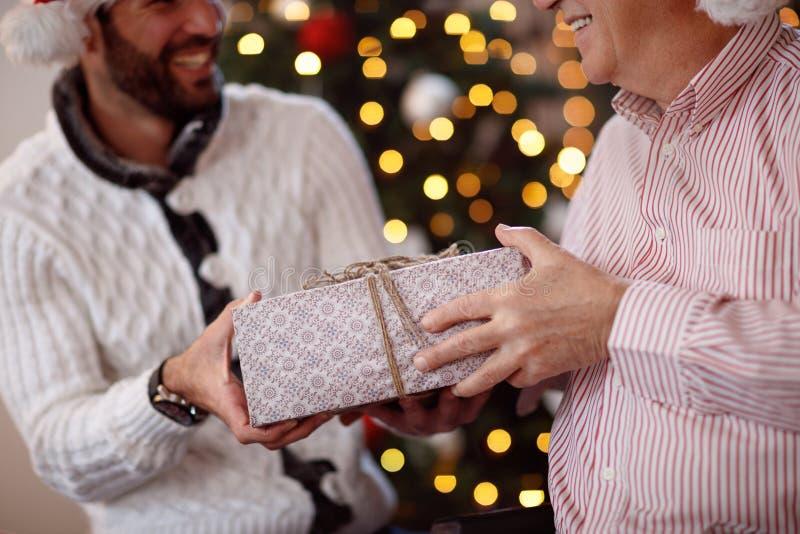 Compartilhando do presente na doação do Natal-pai atual ao filho foto de stock