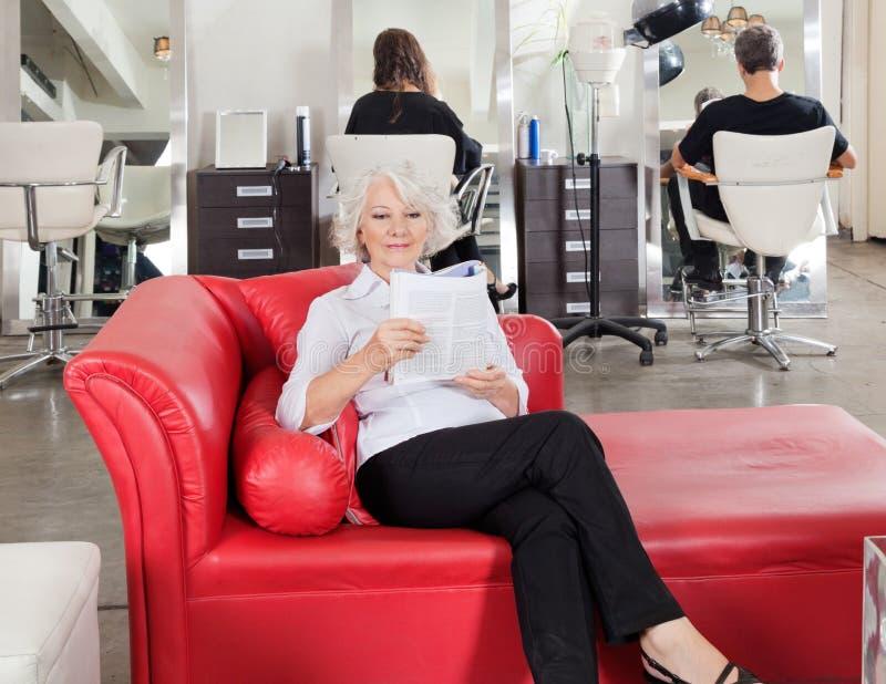 Compartimento da leitura da mulher com os clientes que esperam fotografia de stock