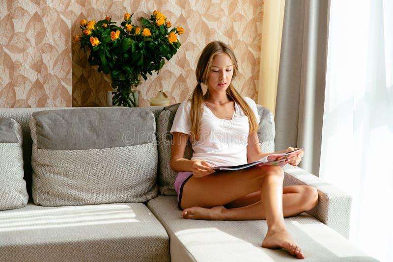 Compartimento da leitura da mulher em casa no sofá foto de stock
