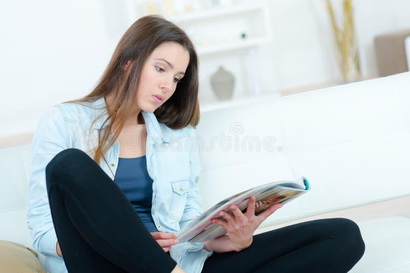 Compartimento feliz bonito da leitura da mulher no quarto foto de stock