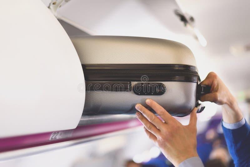 compartimiento del Mano-equipaje con las maletas en aeroplano Las manos sacan el bulto de mano El pasajero puso la cabina del bol fotos de archivo