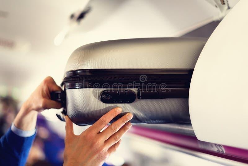 compartimiento del Mano-equipaje con las maletas en aeroplano Las manos sacan el bulto de mano El pasajero puso la cabina del bol imagenes de archivo