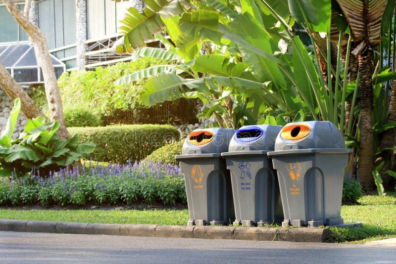 Compartimiento, Trashcan, paseo oblicuo del cubo de la basura de la basura plástica del claro en el público del jardín fotos de archivo