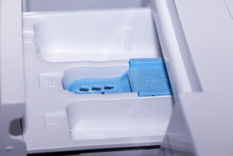 Compartimientos para poner el suavizador y el blanqueo detergentes en una lavadora de ropa automática fotos de archivo libres de regalías