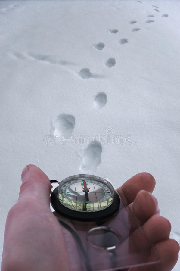 Man with a compass in his hand is looking for the road in the snow stock photos